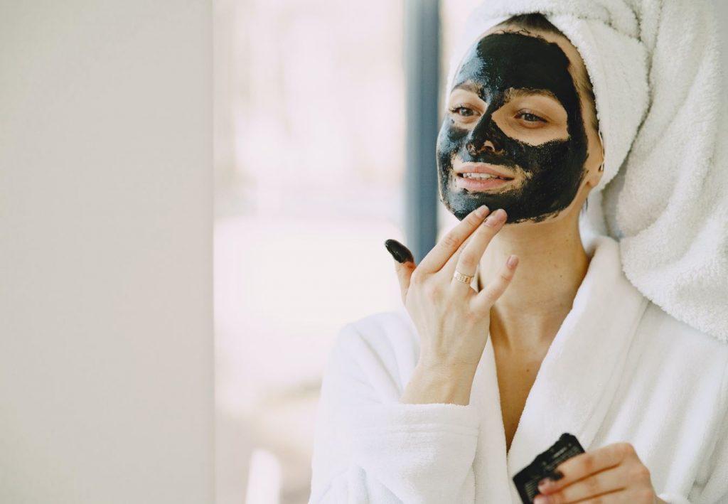 femme appliquant masque au charbon